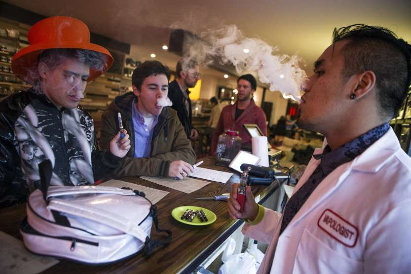 "An employee ""Vapologist"" stands behind the bar as he puffs on an e-cigarette with customers in New York City"