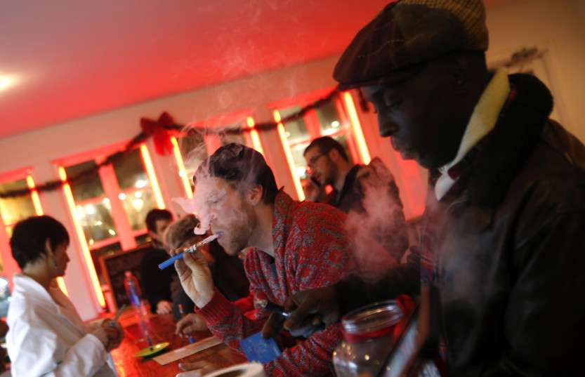 Customers puff on e-cigarettes at the Henley Vaporium in New York City
